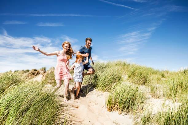Famille qui court dans le sable