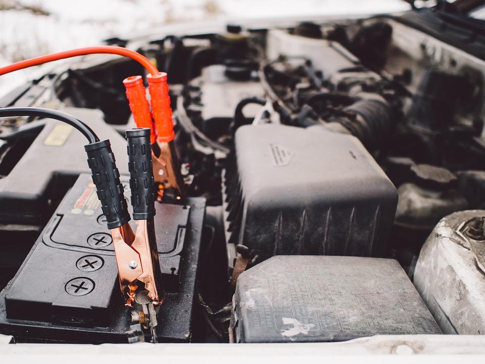 Câbles de démarrage branchés sur une batterie de voiture en panne