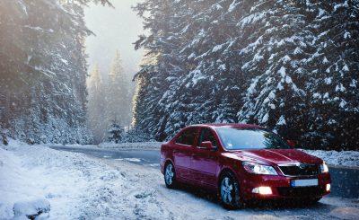 Voiture qui roule sur une route enneigée en hiver