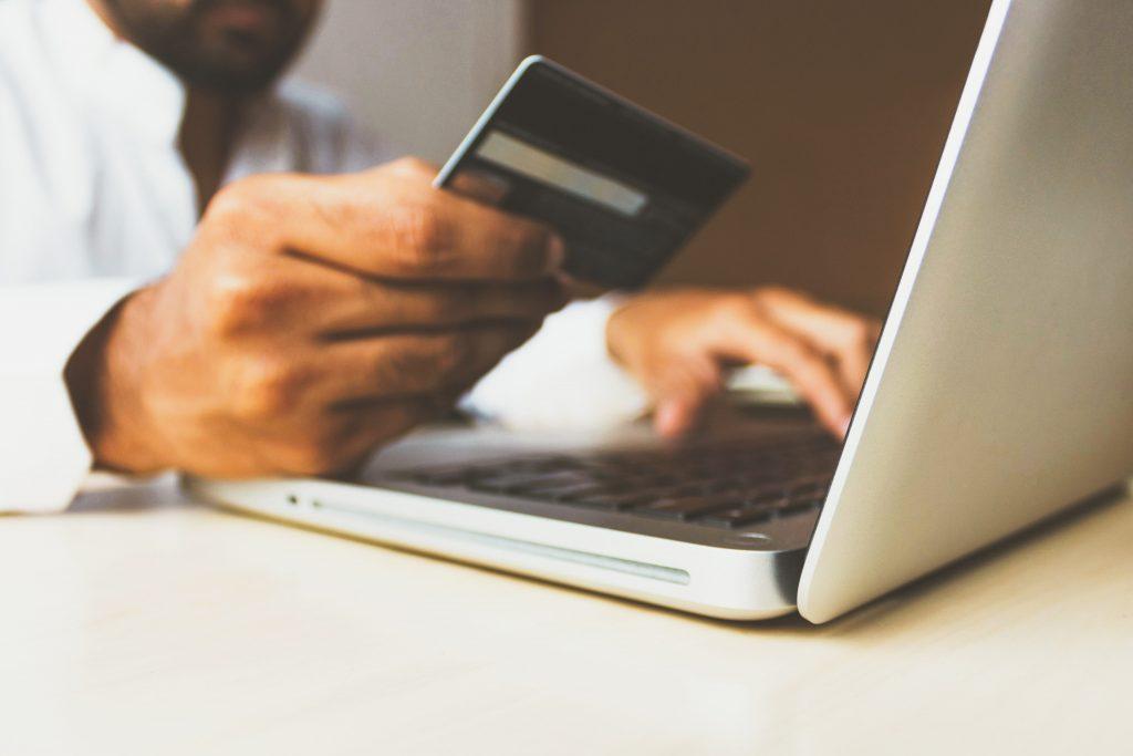un homme avec sa carte bancaire fait un achat en ligne