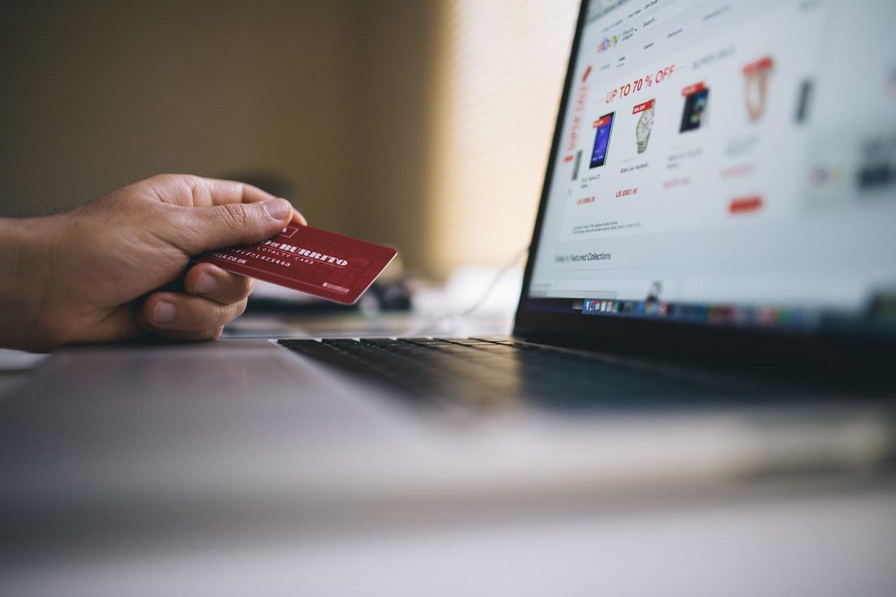 personne qui tient une carte bancaire devant un ordinateur